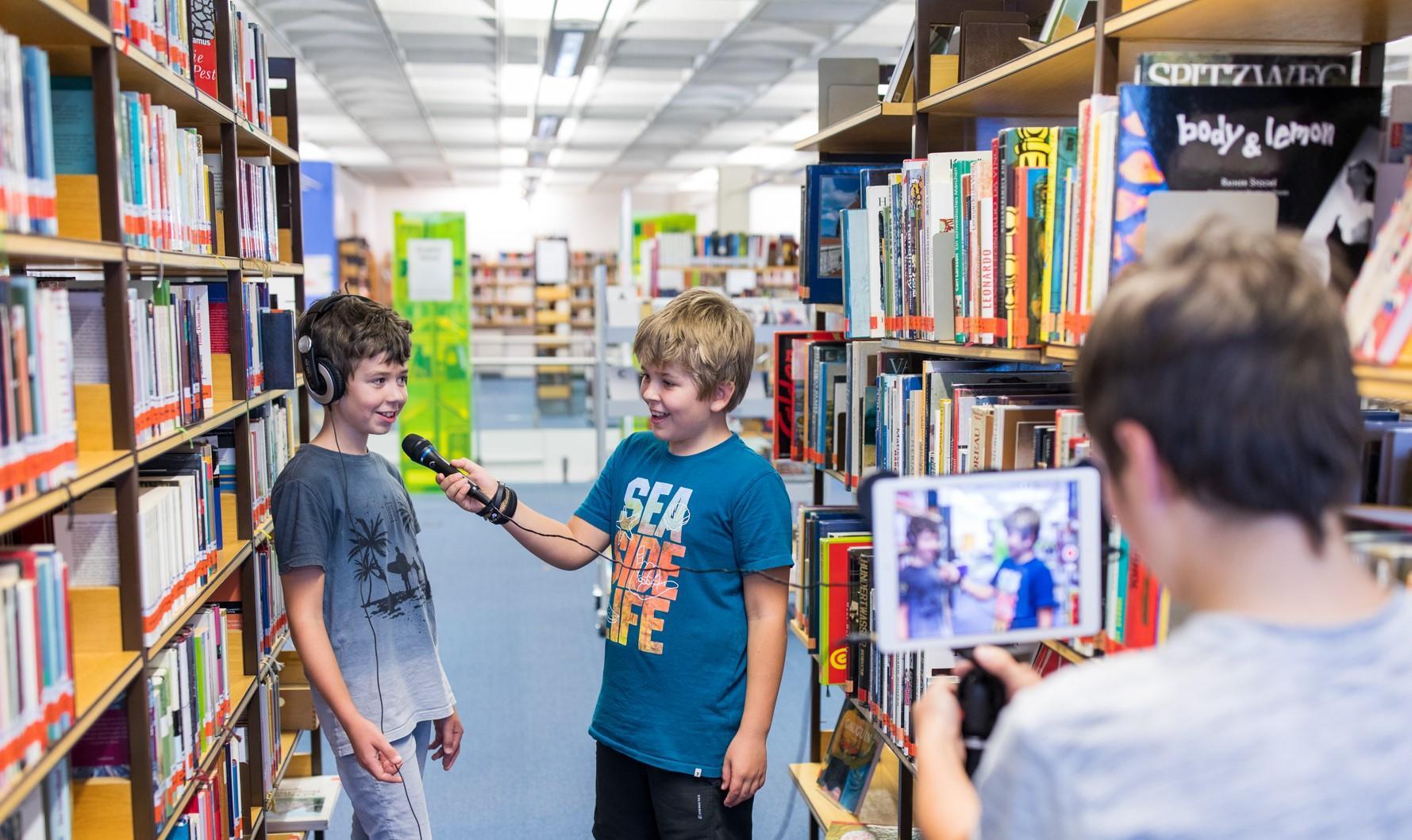 Kinder drehen Film in der Bibliothek