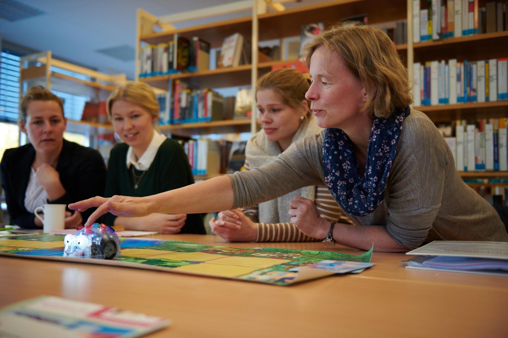 Eine Frau führt in einer Bibliothek einen kleinen Roboter vor Publikum vor.