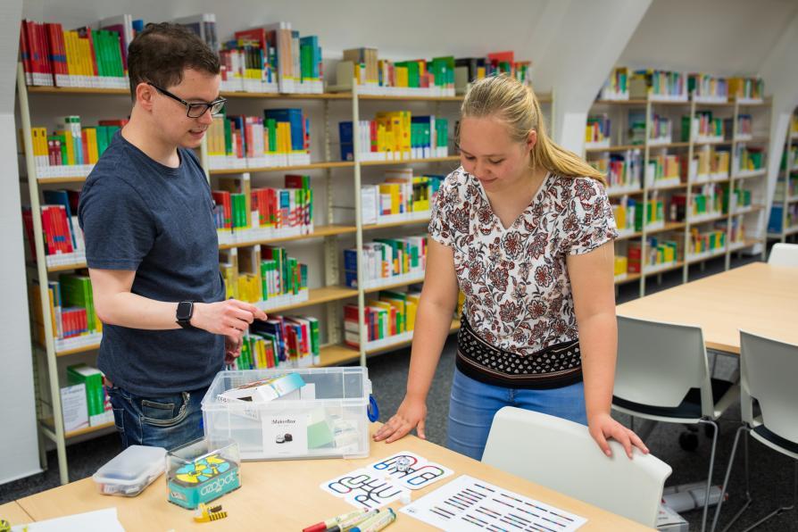 Zwei Personen in einer Bibliothek