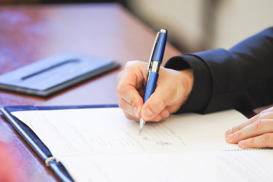 Hand mit Stift unterschreibt Urkunde