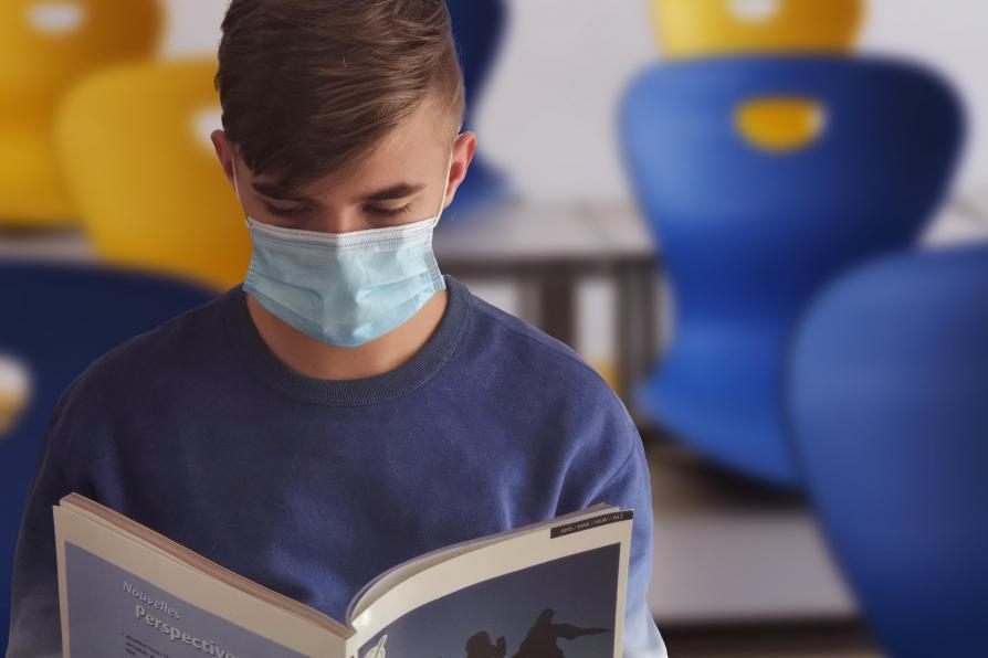 Lesender Schüler mit Maske