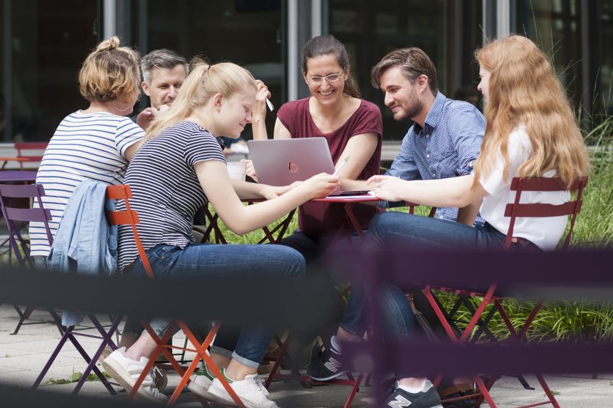 Personengruppe am Tisch im Außenbereich der AGB